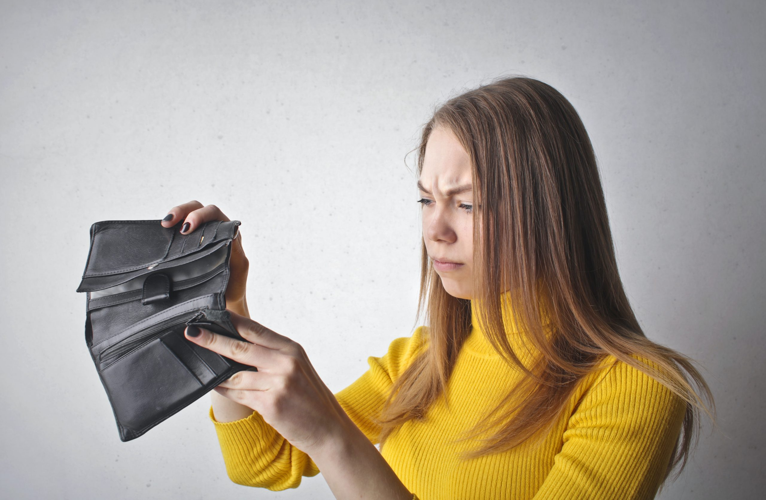 Woman in yellow turtle neck long sleeve shirt opening empty wallet and frowning