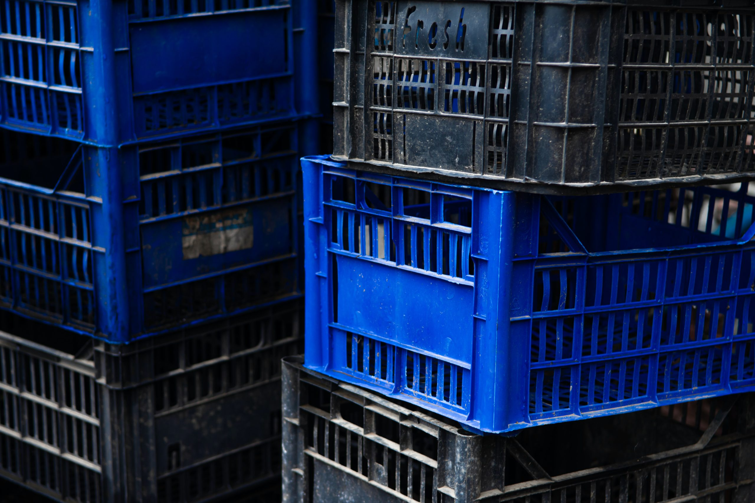 stacked black and blue milk crates